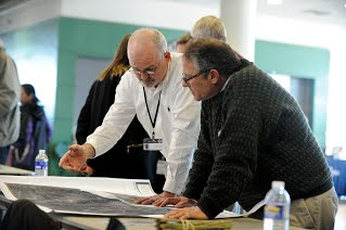 Two men look over a county flood map at an open house