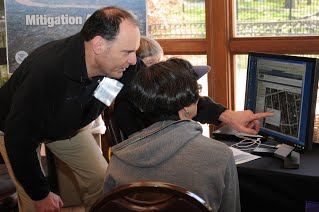 A FEMA representative shows flood hazard data on a computer to one of the people who attended an Open House