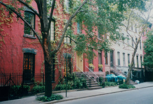 A row of attached residential buildings in a New York City neighborhood.